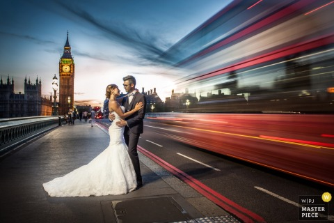 Portrait of the bride and groom on a sidewalk as traffic blows by them by a Miami, FL wedding photographer using a slow shutter speed.