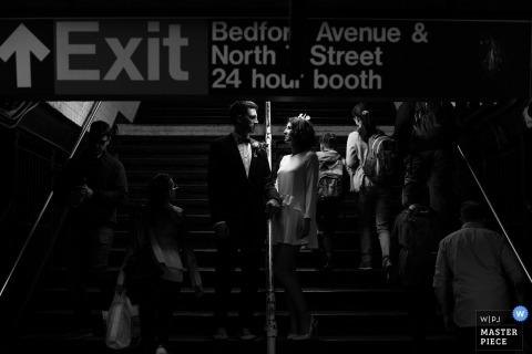 Photo noir et blanc de la mariée et du marié tenant par la main une rampe d'escalier de métro devant un photographe de mariage de Malopolskie, en Pologne.