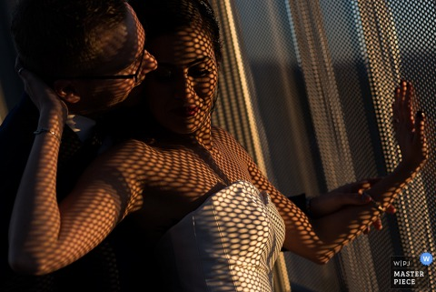 Photo of the bride hugging her groom by a window, covered in shadows from the mesh curtains by a Lake Tahoe, CA wedding photographer.