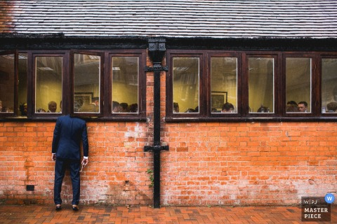 A man standing outside a brick building sticks his head through the window to observe the ceremony in this photo by a Northamptonshire wedding reportage photographer.