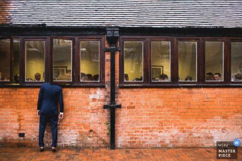 Een man die buiten een bakstenen gebouw staat steekt zijn hoofd door het raam om de ceremonie op deze foto te observeren door een fotograaf van de huwelijksreportage van Northamptonshire.
