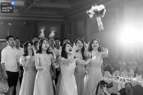 Photo of women trying to catch the bride's bouquet as it flies through the air by a Guangdong, China wedding photographer.
