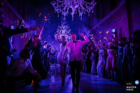 Photo of the bride and groom walking past cheering guests beneath ornate chandeliers by a Venice wedding photographer.