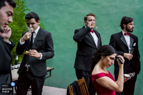 Photo of men having a drink during the reception as a woman touches up her makeup by a Montpellier wedding photographer.