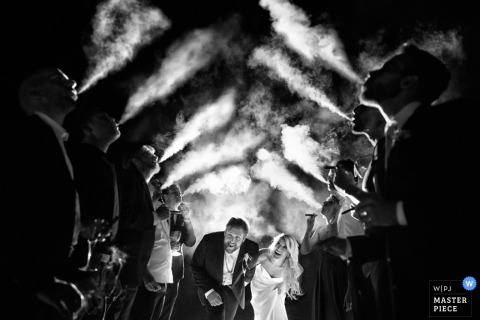 Black and white photo of the bride and groom ducking as they walk between a row of men blowing cigar smoke in the air by a Tuscany wedding photographer.