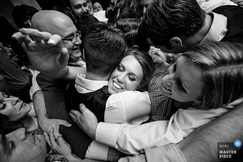 The bride and groom are surrounded by guests hugging them in this black and white photo by a New Jersey wedding photographer.