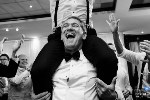 A man hoists another onto his shoulders in this black and white photo by a Montreal, Quebec wedding photographer.