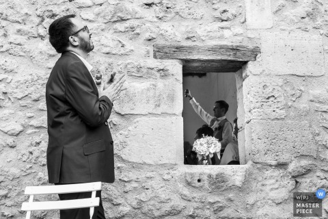 Black and white photo of a man applauding outside the reception as a man giving a toast can be seen through the window by a France wedding photographer.