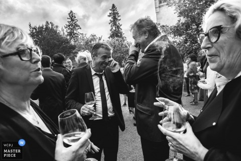 Black and white photos of guests celebrating after the ceremony with champagne by a France wedding photographer.