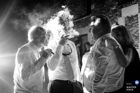 Guests stand smoking cigars as one man's face is shrouded by smoke in this photo by a Nantes wedding photographer.