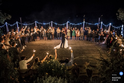 The guests stand in a circle around the dance floor holding sparklers as the bride and groom dance in this photo by a Landes wedding photographer.
