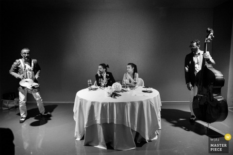 The bride and groom sit at a table as two musicians play on either side of them in this black and white photo by a Calabria wedding photographer.