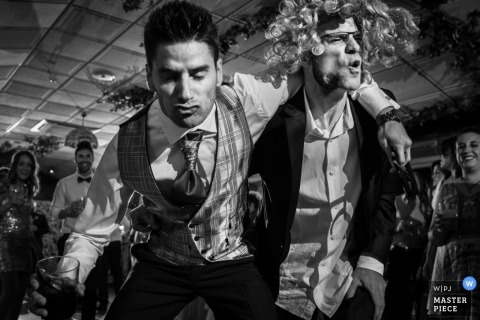 Two men dance on the dance floor as one wears a comical wig in this black and white photo by an Alicante, Valencia wedding photographer.