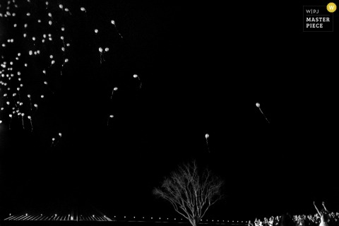 Black and white photo of balloons being released into the clear night sky by a Santa Fe, Argentina wedding photographer.