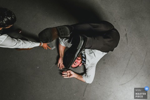 Photo of a man laying on the ground with his feet raised over his head by a San Francisco, CA wedding photographer.