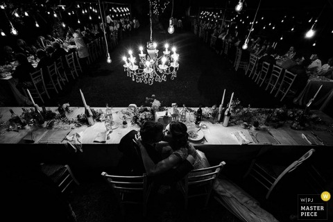 Black and white photo of the bride and groom kissing beneath a chandelier during the reception by a Lecce, Italy wedding photographer.
