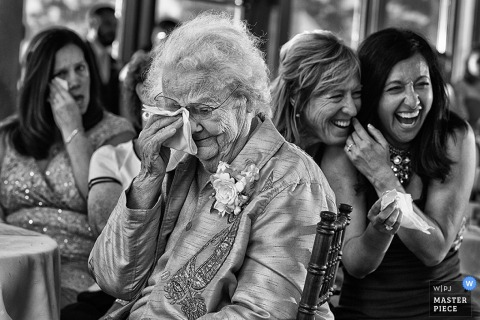 Black and white photo of two women laughing as others dab tears from their eyes during the reception by a Carson City, NV wedding photographer.