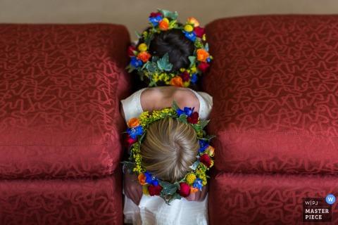 Zdjęcie dwóch młodych dziewcząt w koronach kwiatowych zaklinowanych między poduszkami przez fotografa ślubnego z Missoula, MT.