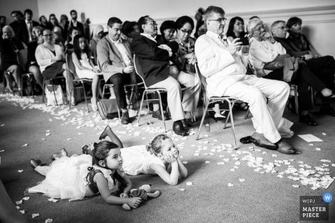 Schwarzweiss-Foto von zwei jungen Mädchen, die auf ihre Mägen im Gang während der Zeremonie von einem Schweiz-Hochzeitsfotografen legen.