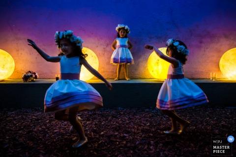 Foto van drie jonge meisjes die in de nacht voor grote, ronde lichten dansen door een huwelijksfotograaf uit Montpellier.