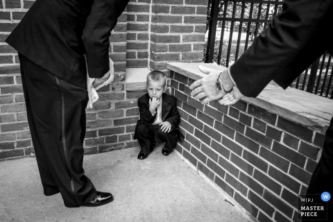 Black and white photo of two men trying to encourage a young boy sitting in the corner by a Cincinnati, OH wedding photographer.