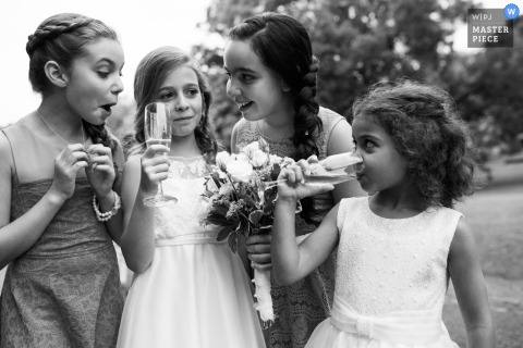 Black and white photo of four young girls with two drinking from champagne glasses by a Montreal, Quebec wedding photographer.