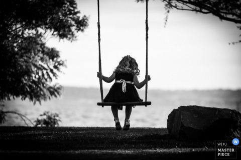 Black and white photo of a little girl sitting on a swing by an Umbria wedding photographer.