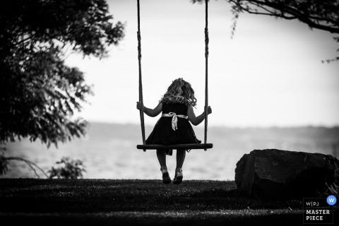 Photo noir et blanc d'une petite fille assise sur une balançoire par un photographe de mariage en Ombrie.