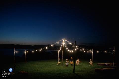 Eine Gruppe von Kindern spielt draußen in der Nacht unter Lichterketten auf diesem Foto eines Hochzeitsfotografen aus Rom.