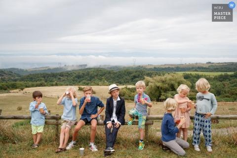 Foto de niños sentados en una valla frente a un campo por un fotógrafo de bodas de Amsterdam.
