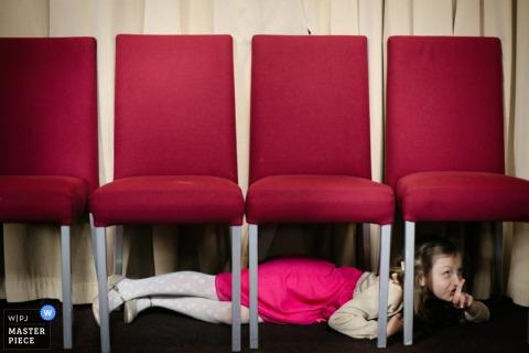 Foto eines jungen Mädchens, das unter Stühlen sich versteckt und einen Finger zu ihren Lippen durch einen Hochzeitsreportagephotographen Londons, England hält.