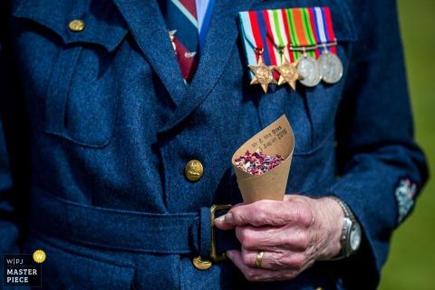 De foto van het detail van een mens in een eenvormig die met verscheidene medailles door een fotograaf van de het huwelijksreportage van Devon, Engeland wordt verfraaid.