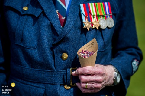 Detail photo of a man in a uniform decorated with several medals by a Devon, England wedding reportage photographer.