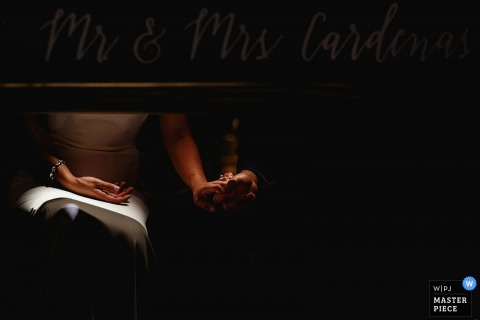 Detail photo of the bride and groom holding hands under the table by an England wedding reportage photographer.