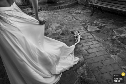 Black and white detail photo of the bride taking off her heels and wedding gown on cobblestone by a Calabria wedding photographer.
