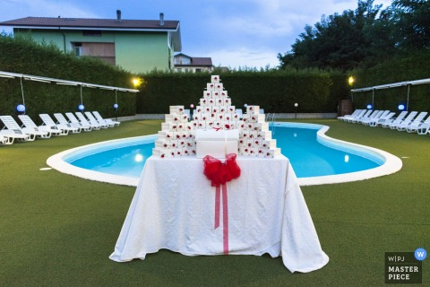 Detail photo of party favors stacked on a white table with a red bow in front of a pool by a Calabria wedding photographer.