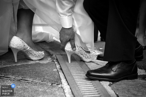 Black and white detail photo of a man helping the bride pull her heel out of a grate by a Piedmont wedding photographer.