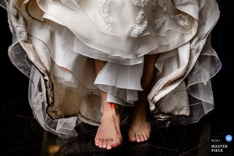 Detail photo of the bride's feet beneath her wedding dress by an Atlantic, NJ wedding photographer.