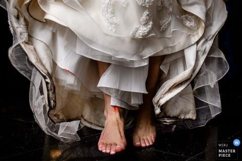 Detail photo of the bride's feet beneath her wedding dress by an Atlantic, NJ wedding photographer.