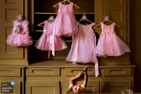 Photo of a young girl in front of five small pink dresses hanging on a wardrobe by a Rotterdam wedding photographer.