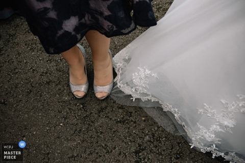 A guest accidentally stands on the bride's dress in this detail photo by a Scotland wedding reportage photographer.