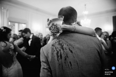 Black and white photo of a guest accidentally spilling a bit of her drink on another as she gives him a hug by a San Francisco, CA wedding photographer.