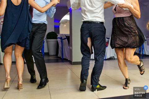 Führen Sie Foto eines Mannes mit einem Riss in der Naht seines Hosenbeins einzeln auf, während er und ein anderes Paar durch einen Krakau-Hochzeitsfotografen tanzen.