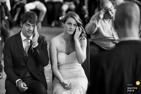The bride and groom sit holding their left hands to their faces in this black and white photo by an Umbria wedding photographer.