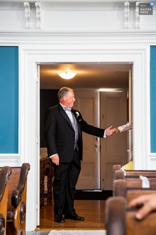 Photo of the bride's father standing in the doorway to the ceremony as the bride gives him her hand by a Tacoma, WA wedding photographer.