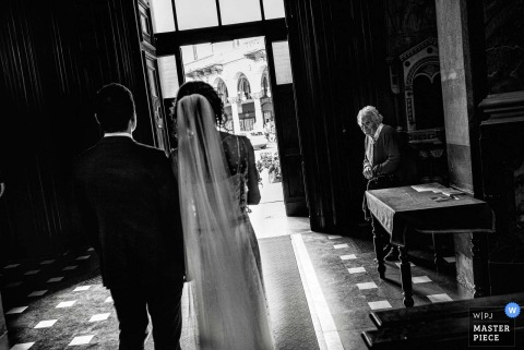 Black and white photo of the bride walking down the aisle during the ceremony by a Piedmont wedding photographer.