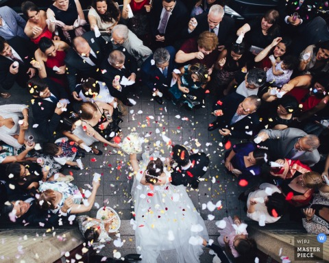 Photo taken above of the bride and groom exiting the ceremony as guests surround them and toss flower petals by a Porto, Portugal wedding photographer.