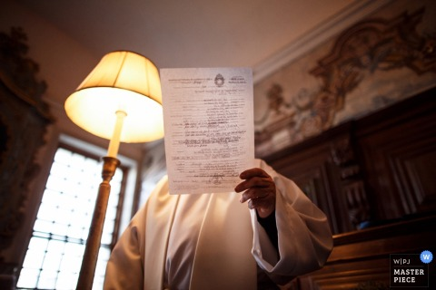 Detail photo of the priest looking over the marriage license before the ceremony by a Porto, Portugal wedding photographer.