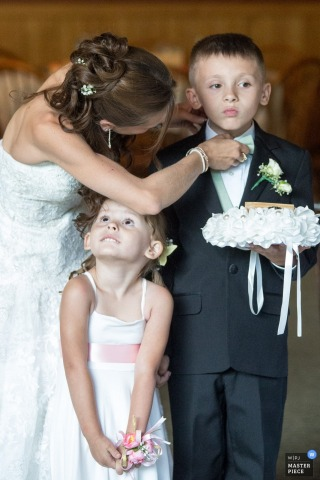 The bride helps the ring bearer adjust his bow tie as the flower girl looks up at her in this photo by a Buffalo, NY wedding photographer.