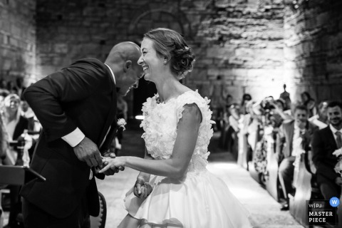 Black and white photo of the bride laughing as the groom puts on her wedding ring by a Lombardy wedding photographer.
